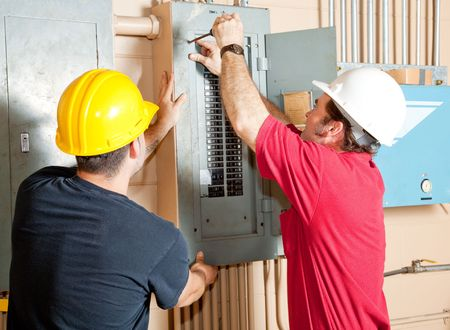 Electricians working together to repair an industrial circuit breaker panel.