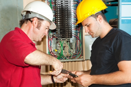 journeyman: Electrician and apprentice repairing a circuit breaker from an industrial panel.