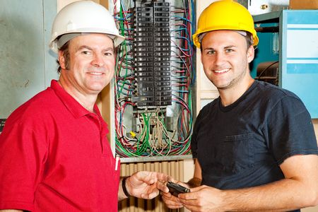 energy work: Friendly master electrician and apprentice working on breaker panel.