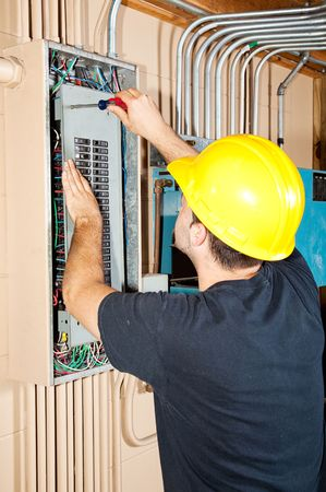 panel: Electrician working on a breaker panel in a control room filled with exposed pipe.