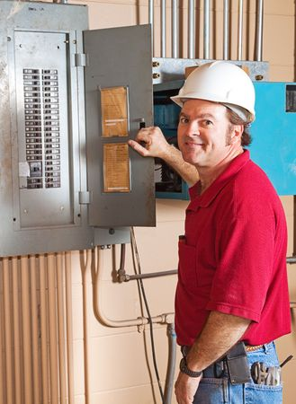 Industrial electrician working on a breaker panel.   Banque d'images