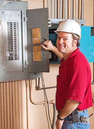 Electricista industrial trabajando en un interruptor del panel. Foto de archivo - 4685119