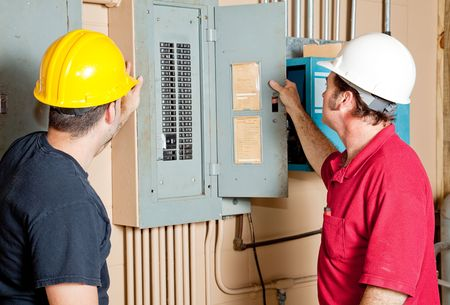 Electricians examining a circuit breaker panel in an industrial setting.   Stockfoto