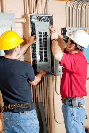Two electricians repairing an electrical circuit breaker panel in an industrial setting.