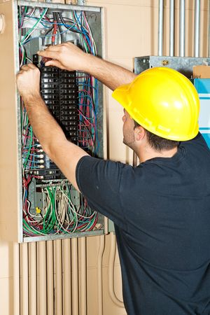 Electrician changing a breaker in a large industrial breaker panel.