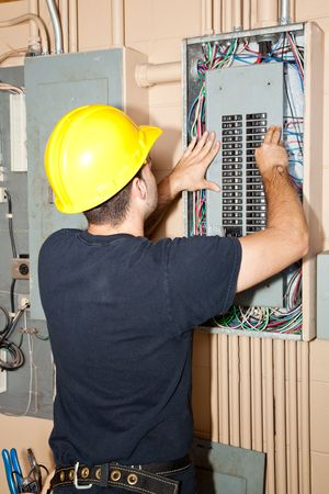 panel: Electrician repairing circuit breakers in industrial electric panel.