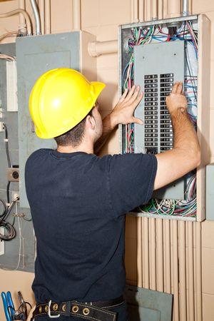 cinturon seguridad: Electricista en la reparaci�n de los disyuntores el�ctricos industriales del panel.