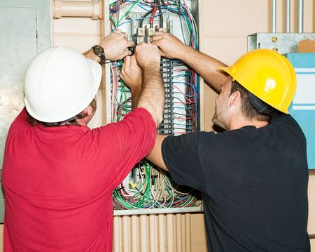 Journeyman and apprentice electrician working to repair a circuit breaker panel.
