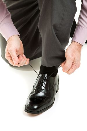 shoe strings: Man lacing up his shiny new black dress shoes.  Isolated on white.