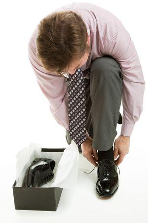 shoe boxes: El hombre vestido con traje de negocios tratando de un nuevo par de zapatos de vestir. Aislado en blanco. Foto de archivo