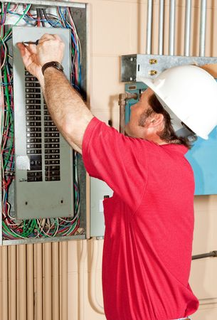 licensed: Licensed master electrician working on an industrial breaker panel.