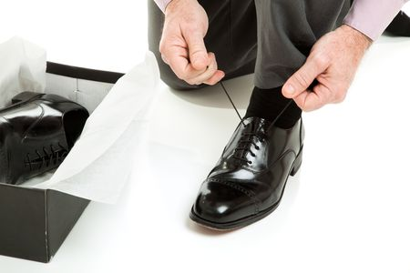 Closeup of a mans hands tying the laces on a new pair of shoes.   photo