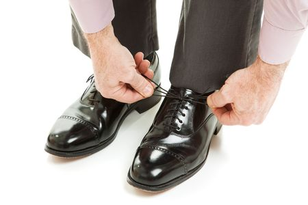 shoe strings: Closeup of a mans hands as he ties his shiny new dress shoes.  Isolated on white.