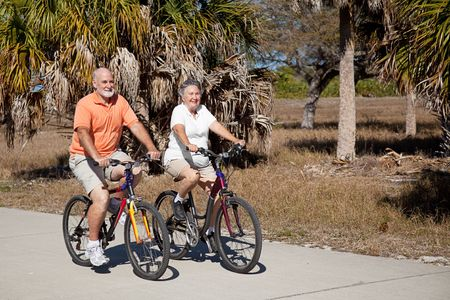 Happy senior couple gets in shape riding their bicycles.   photo
