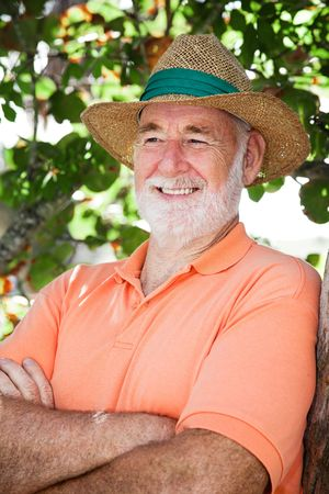 Handsome senior man in a straw hat looking off camera.