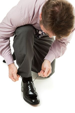 tying: Businessman lacing up his shiny black leather shoes.  Isolated on white
