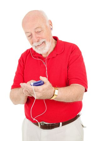 Senior man browsing his music collection on his mp3 player.  Isolated on white.   photo