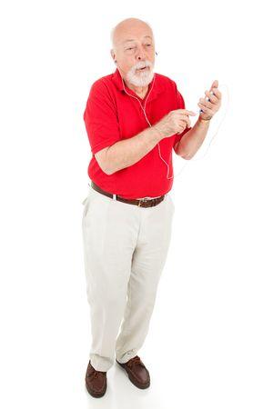khaki pants: Full body isolated view of a senior man enjoying tunes on his mp3 player.