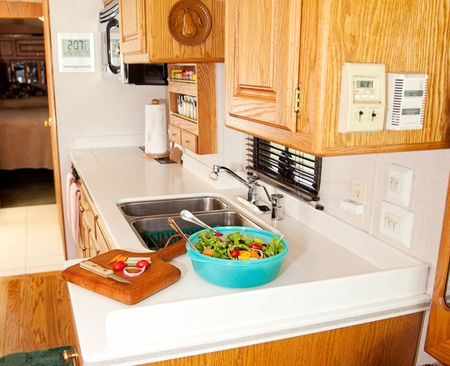recreational vehicle: Salad and cutting board with veggies in the compact kitchen of a recreational vehicle.