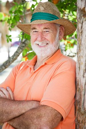 retired man: Portrait of a handsome senior man in a Panama hat leaning against a tree.