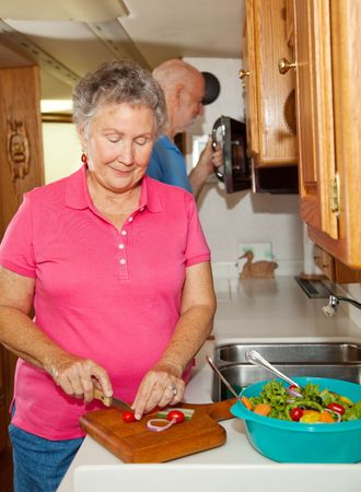 Retired senior couple cooking together in the kitchen of their motor home.   photo
