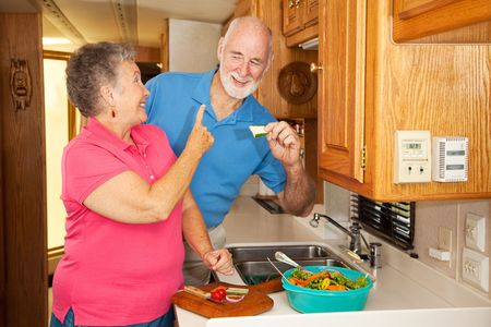 Retired senior couple making lunch in their motor home kitchen.  The husband cant wait for lunch. photo