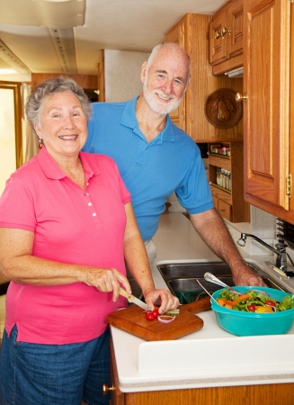 Senior couple in the kitchen of their motor home preparing lunch.   photo