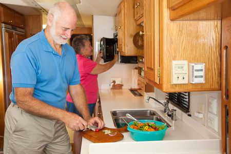 Senior couple in prepares a meal together in their RV camper kitchen.   photo