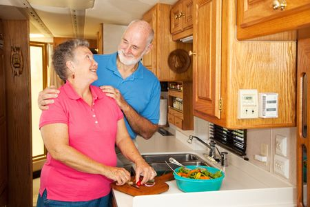 Senior couple get romantic while preparing lunch in their RV.