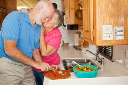 Senior man helping his wife in the kitchen of their RV gets rewarded with a kiss.