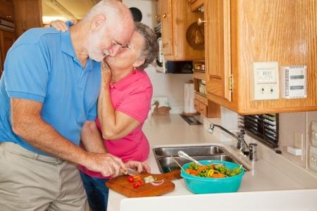 rewarded: Superior hombre ayudar a su esposa en la cocina de su RV se recompensa con un beso. Foto de archivo