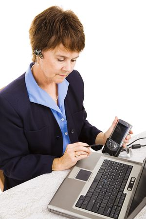 Businesswoman transferring data from her PDA to her laptop while talking on hands free set. Stock Photo - 4810438
