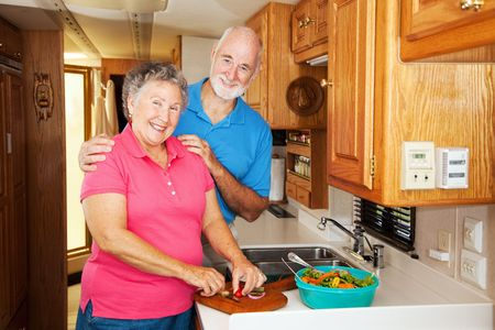 Senior couple cooking together in the kitchen of their motor home.   photo