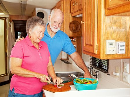 Senior couple preparing a healthy lunch in their motor home kitchen photo