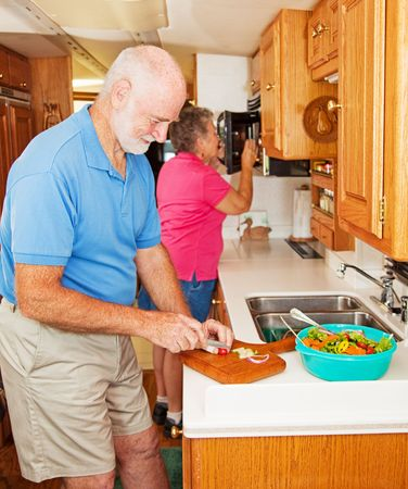 Senior couple cooking healthy dinner in the kitchen of their RV.   photo