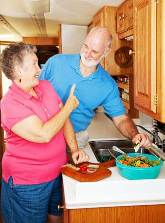 Senior lady playfully scolding her husband for snatching a cucumber from the salad she is making.   photo