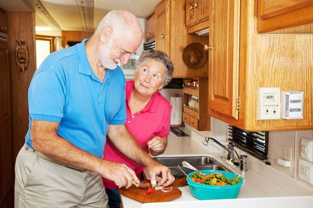 Senior woman thanking her husband for helping prepare dinner in their RV kitchen. photo