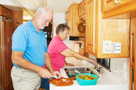 Senior couple cooking in the kitchen of their motor home.  photo