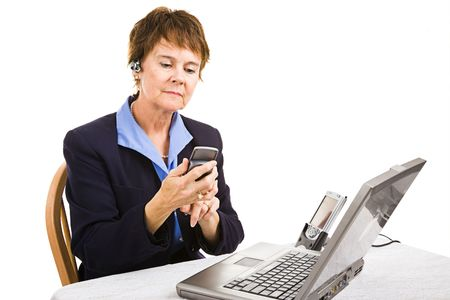 Mature businesswoman using her cellphone, PDA, and laptop computer all at once. Stock Photo - 4810512