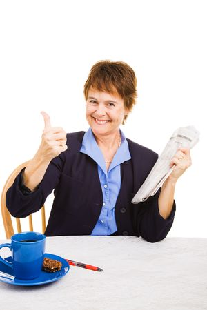 Mature woman looking for a job in the newspaper classified section is optimistic about finding work.   photo
