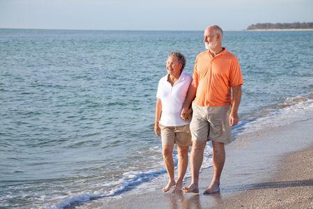 stroll: Happy senior couple enjoys a romantic stroll on the beach. Stock Photo