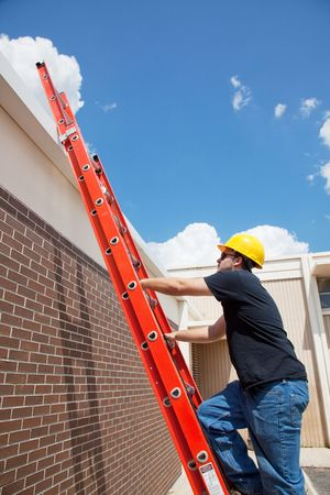 ladder safety: Construction worker climbing up a ladder to the roof of a building.