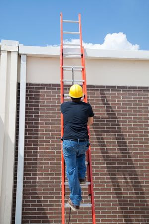 ladder safety: Construction worker climbing a ladder to the roof of a building. Stock Photo