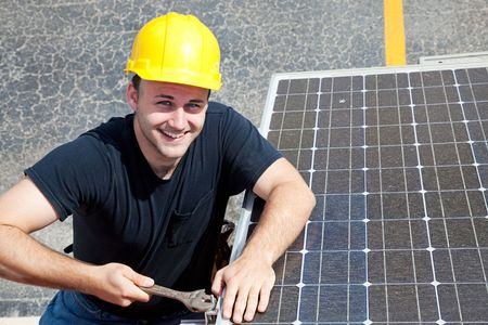 Handsome young electrician smiling as he installs solar panels on the side of a building. photo