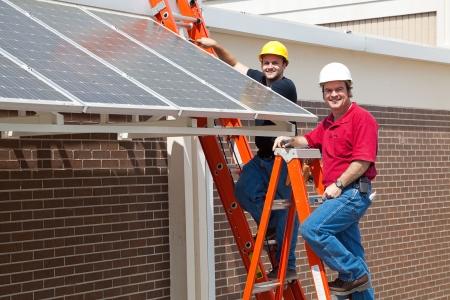 幸せな電気技師は新しい緑の経済にエネルギー効率の高い太陽電池パネルをインストールするために採用します。