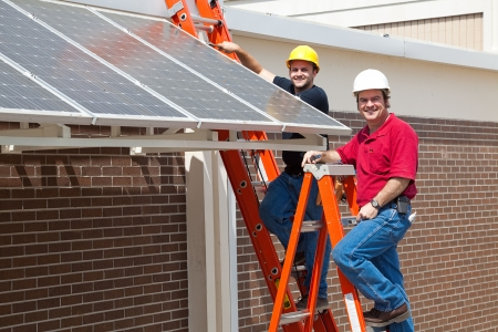 energy work: Happy electricians employed to install energy efficient solar panels in the new green economy.