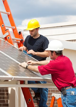 Electricians working to install solar panels on the side of a building.