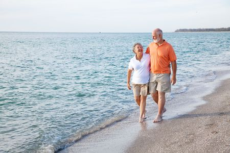 retired: Beautiful senior couple takes a romantic stroll on a tropical beach.