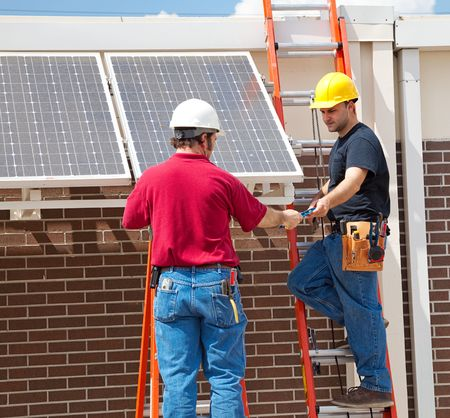 journeyman: Two electricians installing solar panels on the side of a building. Stock Photo