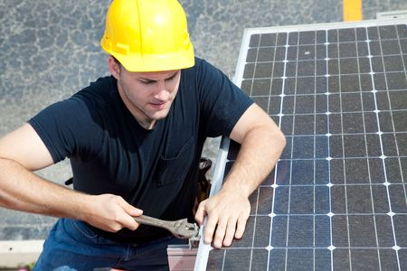 Green job series - young electrician repairs solar panel.   photo
